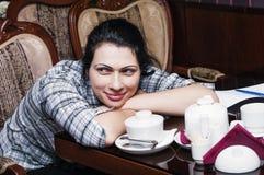 Het dromen vrouwenzitting bij een lijst in een koffie stock afbeeldingen