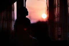 Het dromende meisje ontmoet rode dageraadzitting dichtbij het venster royalty-vrije stock afbeelding