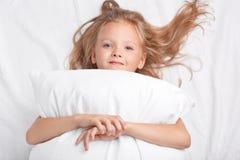 Het dromerige blauwe eyed vrouwelijke jonge geitje met licht haar, omhelst hoofdkussen, bekijkt positief camera, stelt op wit bed royalty-vrije stock foto's