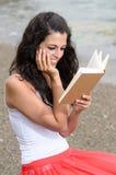 Het dromerige boek van de meisjeslezing bij strand Stock Fotografie