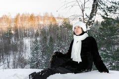 Het dromerige jonge meisje situeert op sneeuw in bos van de de winter het zonnige avond en kijkt omhoog Royalty-vrije Stock Foto