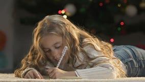 Het dromerige meisje schrijven laatstgenoemde aan Kerstman die om gift, geloof in mirakel, kinderjaren vragen stock video