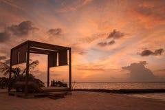 Het dubbel sunbed silhouet tijdens zonsondergang op een tropische plaats stock foto's