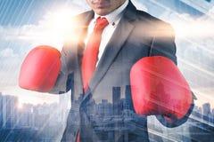 Het dubbele blootstellingsbeeld van de zakenman die een in dozen doende mitts bekleding met cityscape beeld dragen het concept he stock afbeeldingen