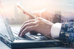 Het dubbele blootstellingsbeeld van de zakenman die een laptop computer met behulp van tijdens zonsopgangbekleding met cityscape  royalty-vrije stock afbeelding
