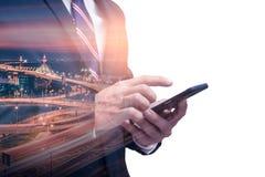 Het dubbele blootstellingsbeeld van de zakenman die een smartphone gebruiken tijdens zonsopgangbekleding met cityscape beeld Het  royalty-vrije stock fotografie