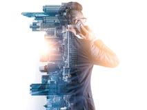 Het dubbele blootstellingsbeeld van de zakenman die een smartphone gebruiken tijdens zonsopgangbekleding met cityscape beeld royalty-vrije stock afbeeldingen