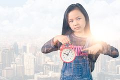 Het dubbele blootstellingsbeeld van het meisjepunt aan een wekker en bekleding met cityscape beeld het zwakke concept school, stock illustratie