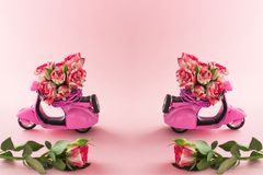 Het Dubleboeket van rozenbloem in mand op achterbank van leuke roze autoped en groot nam op roze achtergrond toe stock afbeelding