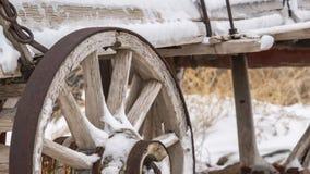 Het duidelijke Panorama een oude houten wagen met roestige wielen bestrooide met sneeuw in de winter stock foto's