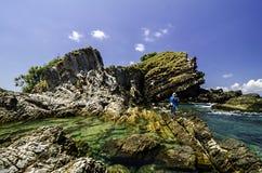 Het duidelijke zeewater omringde rotsachtig eiland met blauwe hemelachtergrond bij zonnige dag Stock Afbeeldingen