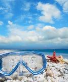 Het duiken masker en shells onder wolken stock foto