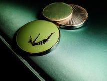 Het duiken poeder compact op groene achtergrond Stock Foto's