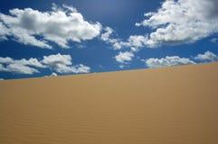 Het duin van de woestijn en witte wolken Royalty-vrije Stock Foto's