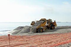 Het Dumpende Zand van de stortplaatsvrachtwagen op het Strand Stock Foto's