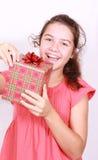 Het durvende meisje opent gift Stock Afbeeldingen