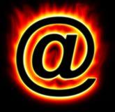 Het e-mail symbool branden met gele rode vlam Stock Foto's