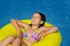 Het echte aanbiddelijke meisje ontspannen in zwembad Stock Fotografie