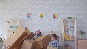 Het echtpaar met dozen in hun handen valt onhandig langzame mo stock videobeelden