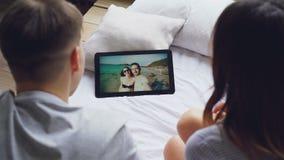 Het echtpaar spreekt aan vrienden op skype gebruikend tablet, lachen de gelukkige minnaars en kussen op het scherm met stock videobeelden