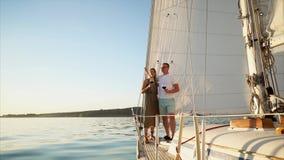 Het echtpaar vaart samen aan boord rivier en drinkt wijn stock video