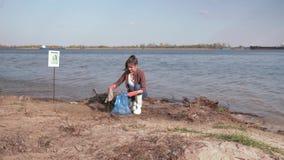 Het ecologische probleem oplossen, jonge vrouwenvrijwilliger maakt vuil strand schoon en verzamelt plastic afval in vuilniszak en stock videobeelden