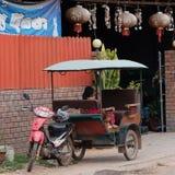 Het een weinig Aziatische meisje zit in een motoriksja dichtbij een huis met rode lantaarns stock foto's