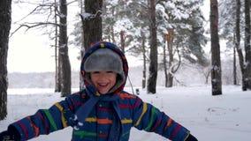 Het een weinig gelukkige kind loopt om de camera onder de snow-covered bomen in de winter te ontmoeten Het concept familie, openl stock videobeelden