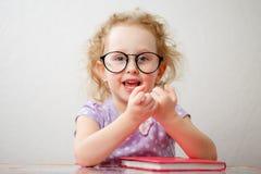 Het een weinig grappige meisje met glazen gaat een boek lezen royalty-vrije stock afbeelding