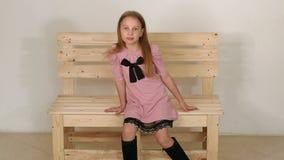 Het een weinig leuke meisje zit op een houten bank in de Studio tegen een witte muur stock footage