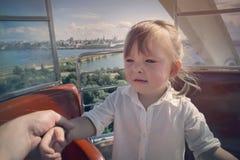 Het een weinig mooie meisje is een beetje bang om een Reuzenrad te berijden Haar hand wordt gehouden door Papa Het concept kinder Stock Foto