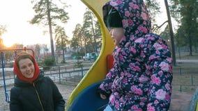 Het een weinig mooie meisje naast haar moeder in een kleurrijk jasje zit op een heuvel in een de lentepark met lange pijnbomen bi stock footage