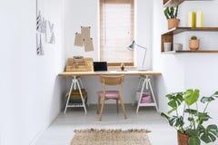Het eenvoudige binnenland van het huisbureau in een heldere ruimte met een bureau, vensterzonneblinden en installatie stock foto