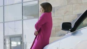 Het eenzame jonge vrouw verpakken in haar roze laag, koude en vermoeid om in openlucht te wachten stock videobeelden