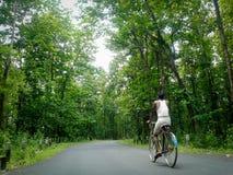 Het eenzame landelijke mens cirkelen in het bos, Landelijke Assamese-mens cyling in een duidelijke weg in Rani Forest, Assam Royalty-vrije Stock Afbeeldingen