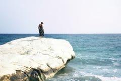 Het eenzame meisje in kleding en met kort kapsel bevindt zich op een witte die rots door de Middellandse Zee, het landmar strand  royalty-vrije stock foto's