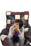 Het eenzame meisje zit op de bank bij studio Stock Foto's