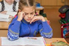 Het eerste nivelleermachinemeisje voelt slecht in klaslokaal op school stock afbeelding