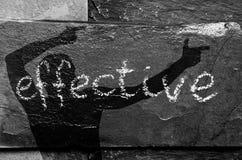 Het EFFICIËNTE woord geschreven met krijt op zwarte steen met mensenschaduw op het Royalty-vrije Stock Foto