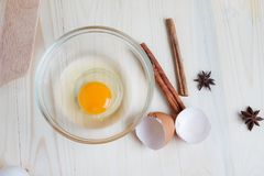Het ei op duidelijke glaskom over houten besnoeiingsraad met bakkerij ingred Stock Fotografie