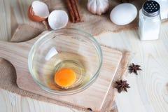 Het ei op duidelijke glaskom over houten besnoeiingsraad met bakkerij ingred Royalty-vrije Stock Fotografie