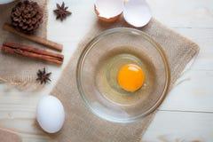 Het ei op duidelijke glaskom over houten besnoeiingsraad met bakkerij ingred Royalty-vrije Stock Foto