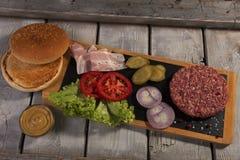 Het eigengemaakte broodje van hamburger verse ingrediënten, gezouten komkommer, rundvleespasteitjes, bacon Royalty-vrije Stock Fotografie