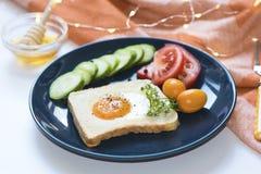 Het eigengemaakte ei in een gat met toostbrood en de groenten op een blauwe ceramische plaat met honing op een witte achtergrond, stock foto's