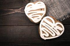 Het eigengemaakte gevormde hart van gemberkoekjes  over houten lijst De dagachtergrond van Valentine Stock Afbeeldingen
