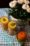 Het eigengemaakte oranje stilleven van het banaansap Stock Foto