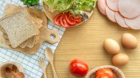 Het eigengemaakte sandwichontbijt voorbereidingen treffen Geheel die tarwebrood op een houten scherpe raad wordt gestapeld Plakto stock foto
