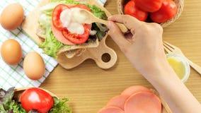 Het eigengemaakte sandwichontbijt voorbereidingen treffen Het gehele tarwebrood wordt op een houten scherpe die raad gestapeld op stock afbeeldingen