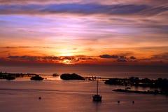 Het eiland en de boot van de zonsondergang Stock Afbeeldingen