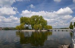 Het eiland onder het meer waarop lange groene bomen tegen een blauwe hemel met wolken kweek stock foto